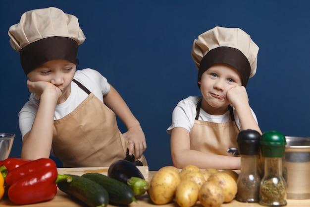 Ritratto di due ragazzini vestiti in uniforme da chef con sguardi annoiati Foto Gratuite