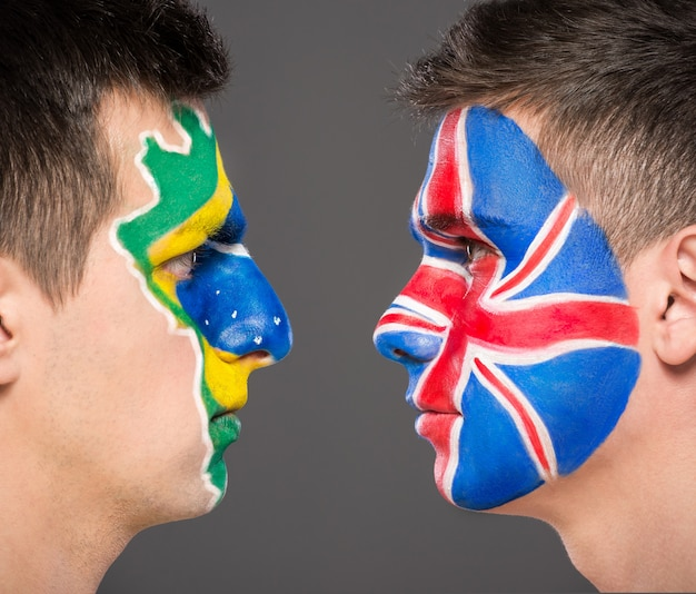 Portrait of two men with painted flags on their faces. Premium Photo