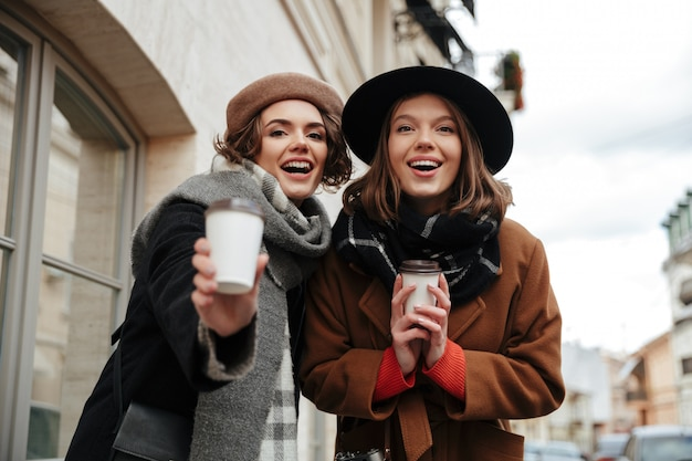 Portrait of two pretty girls dressed in autumn clothes walking Free Photo