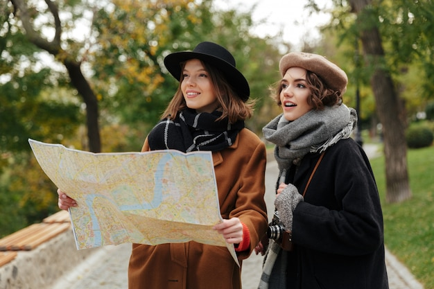 Portrait of two pretty girls dressed in autumn clothes Free Photo