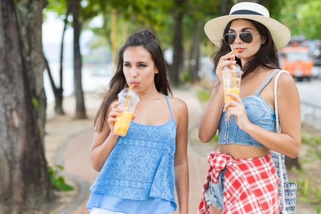 Portrait of two pretty woman drinking fresh juice while walk Premium Photo