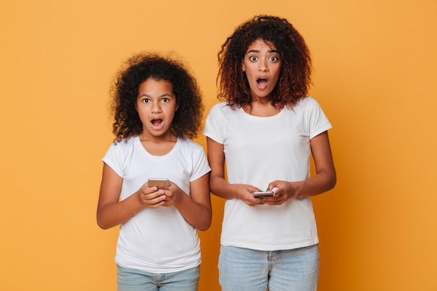 Portrait of a two shocked afro american sisters with smartphones Free Photo