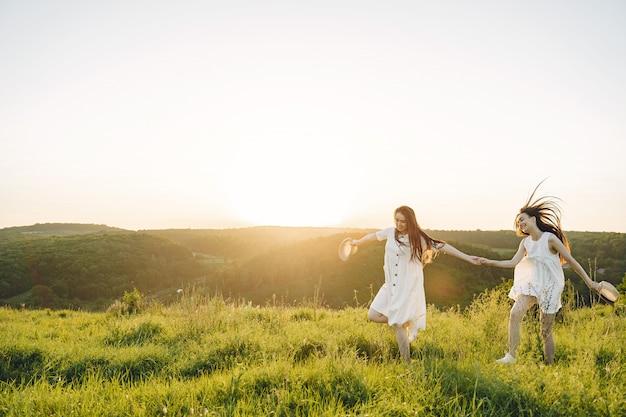 Ritratto di due sorelle in abiti bianchi con i capelli lunghi in un campo Foto Gratuite