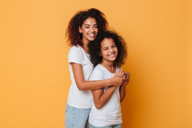 Portrait of two smiling african sisters hugging Free Photo