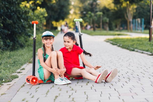 Portrait of two smiling female friends sitting on push scooter Free Photo
