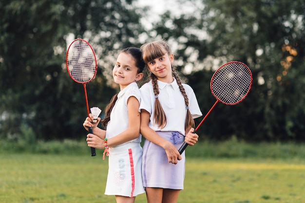 Portrait of two smiling girls holding shuttlecock and badminton in hand Free Photo
