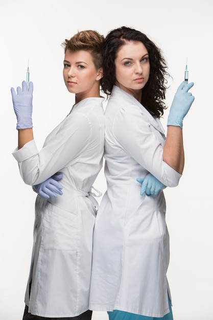 Portrait of two women surgeons showing syringes Free Photo