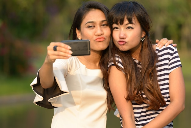 Portrait of two young asian women together relaxing at the park outdoors Premium Photo