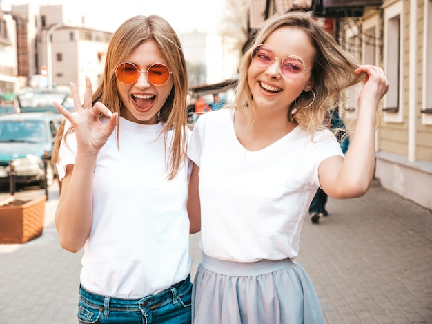 Un ritratto di due giovani belle ragazze sorridenti bionde dei pantaloni a vita bassa in vestiti bianchi della maglietta dell'estate d'avanguardia. . modelli positivi che si divertono in occhiali da sole Foto Gratuite