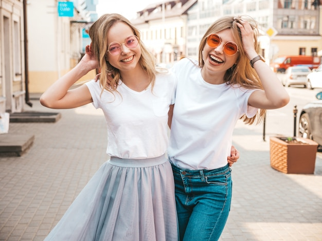Portrait of two young beautiful blond smiling hipster girls in trendy summer white t-shirt clothes.   . positive models having fun in sunglasses.hugging Free Photo