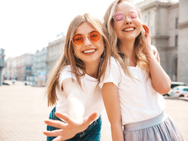 Portrait of two young beautiful blond smiling hipster girls in trendy summer white t-shirt clothes. Free Photo