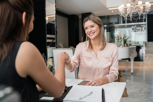 Portrait of two young businesswomen having meeting and shaking hands at hotel lobby. business travel concept. Free Photo