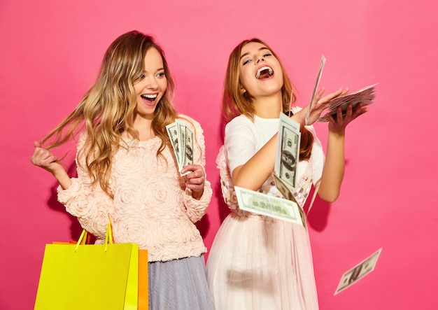 Portrait of two young stylish smiling blond women holding shopping bags. women dressed in summer hipster clothes. positive models spending money over pink wall Free Photo