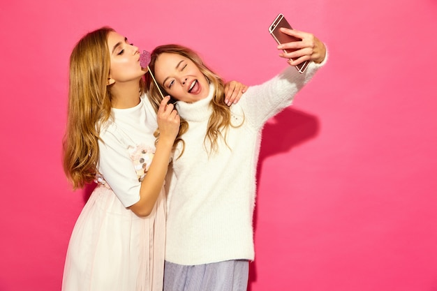 Portrait of two young stylish smiling blond women Free Photo