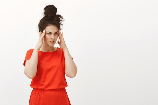 Ritratto di donna caucasica turbata sfocata in abito rosso, tenendo le mani sulle tempie e accigliata dal dispiacere Foto Gratuite