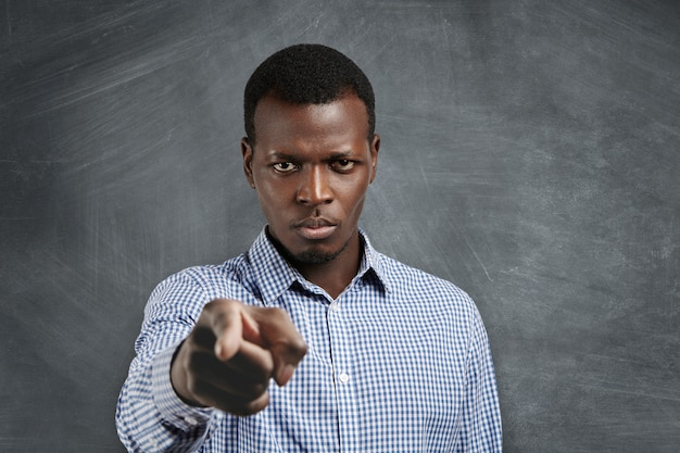 Portrait of unhappy african boss having mad expression pointing his index finger, looking angrily and frowning as if accusing or blaming you for mistake. selective focus on man's face Free Photo