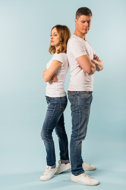 Portrait of unhappy angry young couple standing back to back not ...