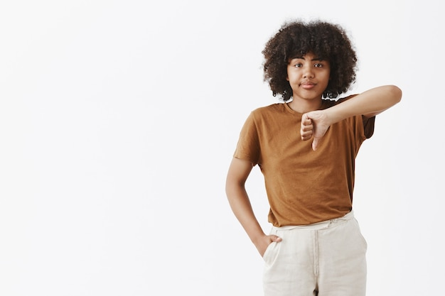 Ritratto di donna afroamericana snob e dispiaciuta non impressionata che è difficile da impressionare sorridendo con disappunto che mostra il pollice verso il basso dall'indifferenza e dal dispiacere Foto Gratuite