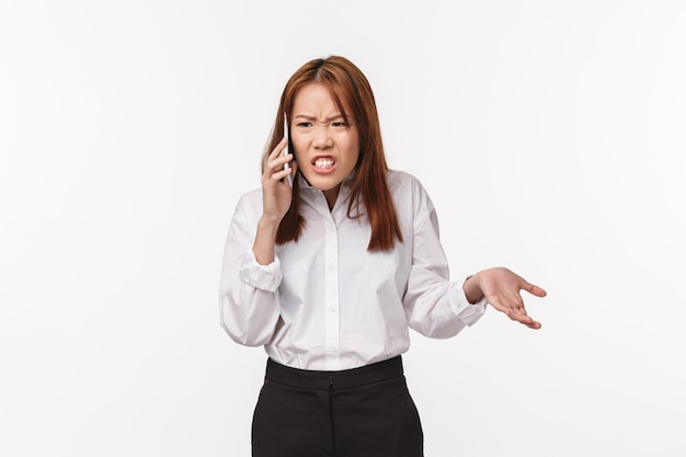 Portrait of unsatisfied angry asian woman talking on phone, grimacing upset and outraged, having tough serious conversation, argument with partner, standing pissed-off Premium Photo