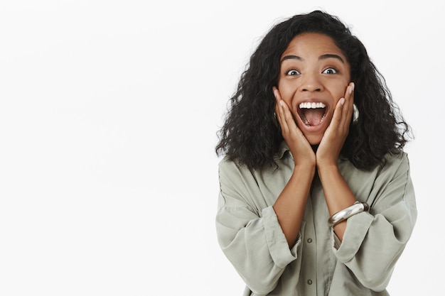 Portrait of upbeat enthusiastic and delighted surprised dark-skinned girlfriend with curly hairstyle yelling from amazement and joy Free Photo