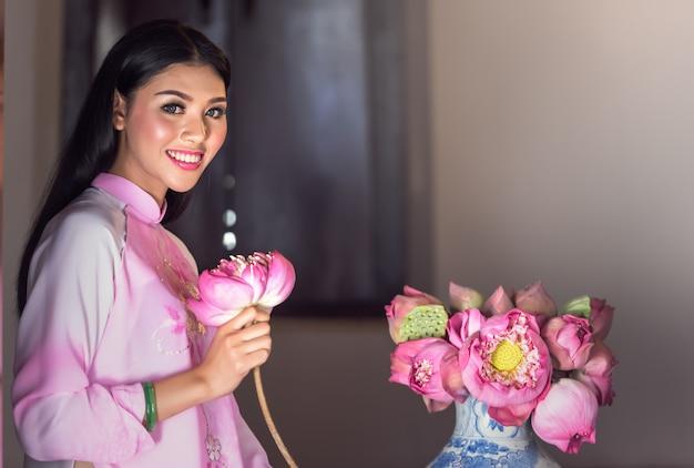 Portrait of vietnamese girl traditional dress with lotus Premium Photo