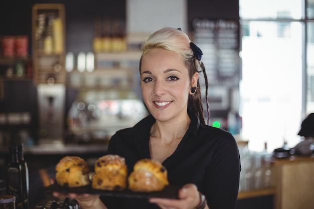 Portrait of waitress holding tray of muffins at counter Free Photo