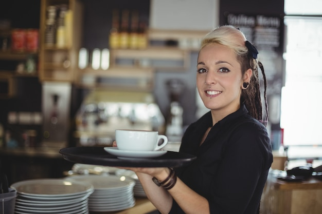 Portrait of waitress standing with cup of coffee Free Photo