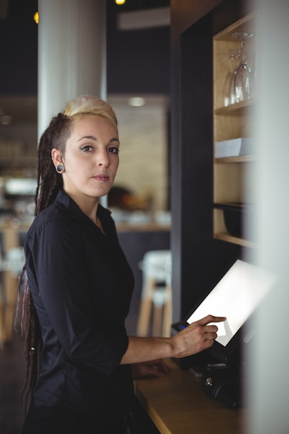Portrait of waitress using cash register at counter Free Photo
