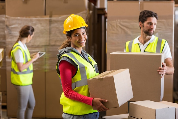 Portrait of warehouse worker carrying a cardboard box Premium Photo