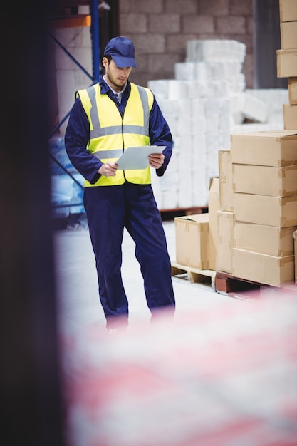 Portrait of warehouse worker with clipboard in warehouse Premium Photo