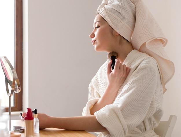 Portrait woman applying blush Free Photo