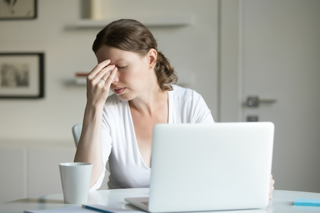Portrait of a woman at desk with laptop, hand at forehead Free Photo