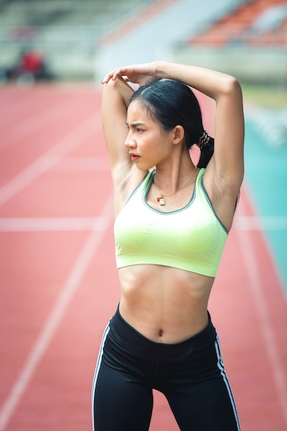 Portrait of woman doing warm up exercises on stadium Free Photo