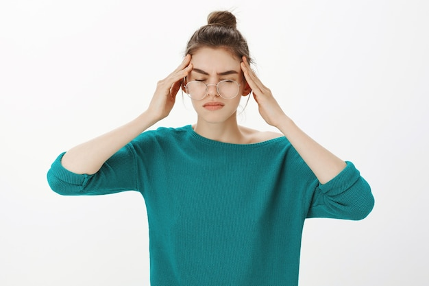 Portrait of woman in glasses having headache, feeling dizzy or have fever, migraine Free Photo