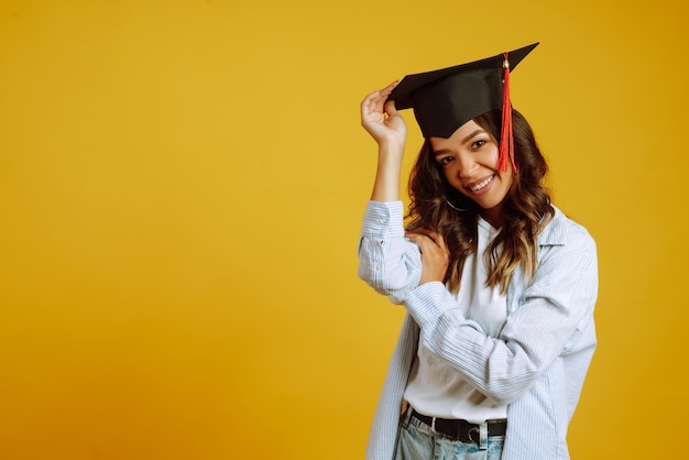 Portrait of woman in a graduation hat on her head posing on yellow. Premium Photo