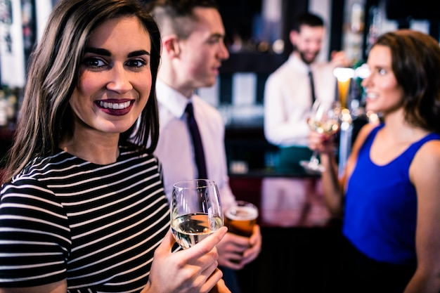 Portrait of woman having a drink with friends in a bar Premium Photo
