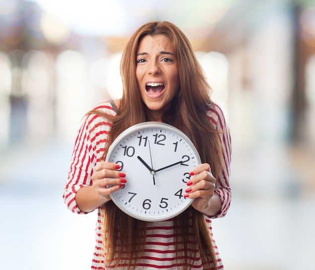Portrait of woman holding clock and screaming Free Photo