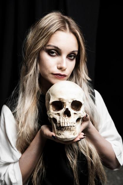 Portrait of woman holding cranium Free Photo