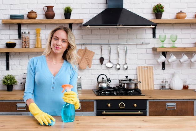 Portrait of a woman holding sponge and detergent spray bottle standing in kitchen Premium Photo