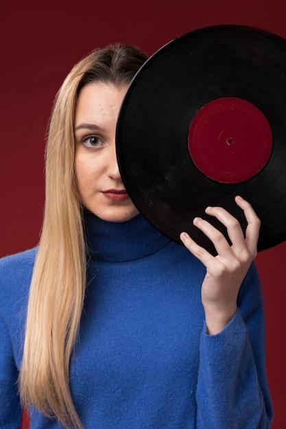 Ritratto di una donna in possesso di un disco in vinile Foto Gratuite