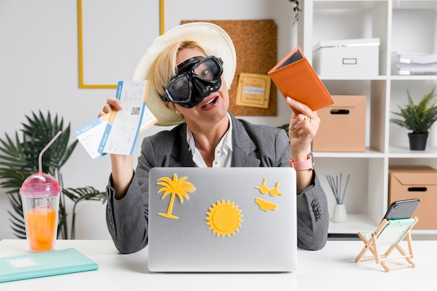 Portrait of woman in office prepared for summer holiday Free Photo