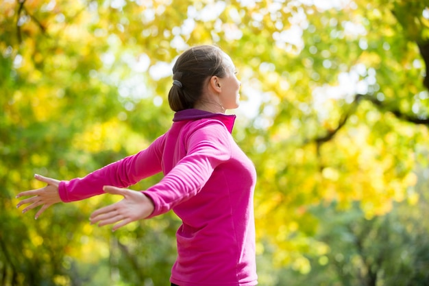 Portrait of a woman outdoors in a sportswear, hands outstreched Free Photo
