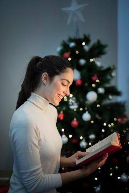 Portrait woman reading next to christmas tree Free Photo