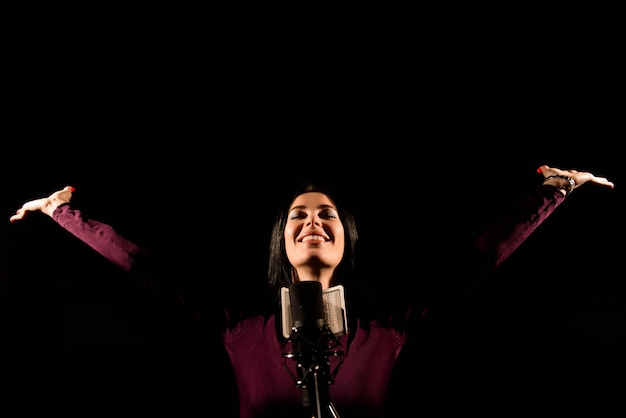 Portrait of woman recording a song in a professional studio Premium Photo