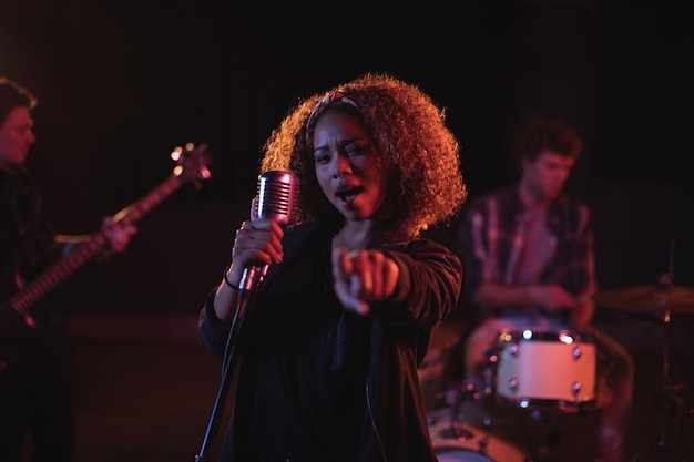 Portrait of woman singing on microphone Free Photo