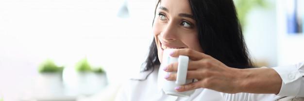 소파에 앉아서 커피를 마시는 세로 여자 프리미엄 사진
