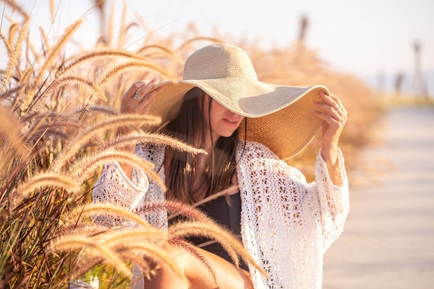 Portrait of a woman in the sun, sitting in a field, dressed in summer clothes and a hat. Free Photo