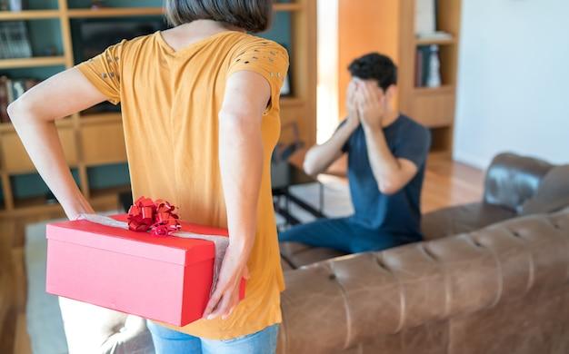 Ritratto di una donna che sorprende il suo ragazzo con un regalo. celebrazione e concetto di san valentino. Foto Gratuite