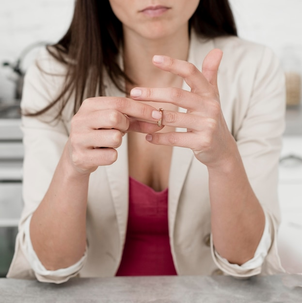 Portrait of woman taking her wedding ring off Free Photo