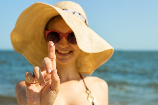 Portrait of woman taking skincare with sunscreen lotion at beach Premium Photo
